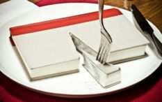 Read a good book lately?  Hardcover book on plate with dinner setting. A slice has been cut out and is ready to eat.